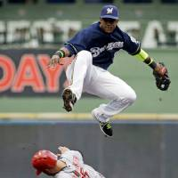 Photo - Milwaukee Brewers shortstop Jean Segura leaps over Cincinnati Reds' Skip Schumaker to turn a double play on a ball hit by Todd Frazier during the first inning of a baseball game Monday, July 21, 2014, in Milwaukee. (AP Photo/Morry Gash)