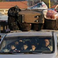 Photo - A Syrian family crosses into Lebanon at the border crossing in Masnaa, eastern Lebanon, Friday, Nov. 30, 2012. Syrian rebels battled regime troops south of Damascus on Friday and Internet and most telephone lines were cut for a second day, but the government reopened the road to the capital's airport in a sign the fighting could be calming, activists said. (AP Photo/Hassan Ammar)