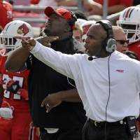 Photo -   Louisville coach Charlie Strong yells instructions to his team from the sidelines during second half of an NCAA college football game against North Carolina in Louisville, Ky., Saturday, Sept. 15, 2012. In the background is Louisville defensive line coach Clint Hurtt. (AP Photo/Garry Jones)