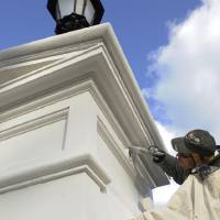 Photo - A painter touches up an entrance post outside the White House in Washington, Friday, Jan. 18, 2013, in preparation for this weekend's 57th Presidential Inauguration, where President Barack Obama will be sworn in for a second term. (AP Photo/Susan Walsh)