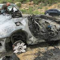 Photo - This photo provided by the Utah Department of Public Safety, shows a damaged vehicle from a head-on collision, Sunday July 6, 2014, in southern Utah.  A van carrying five people was trying to pass a vehicle on U.S. Route 191 when it struck an oncoming sports car holding two people near Monticello, about 285 miles southeast of Salt Lake City, the Utah Highway Patrol said.  Both people in the sports car died after it burst into flames, and three of the van's passengers were killed, Trooper Evan Kirby told KSL-TV. The other two passengers in the van were sent to the hospital in critical condition. (AP Photo/Utah Department of Public Safety)