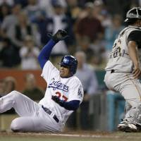 Photo - Los Angeles Dodgers' Matt Kemp, left, scores past Pittsburgh Pirates catcher Ronny Paulino, right, on a single by Andre Ethier in the sixth inning of a major league baseball game Saturday, June 24, 2006, in Los Angeles. (AP Photo/Danny Moloshok) ORG XMIT: LAD118