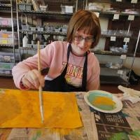 Photo - Heather Cwayna paints during an arts and crafts class at Wings. The Edmond organization helps special needs adults find a place to belong after high school.