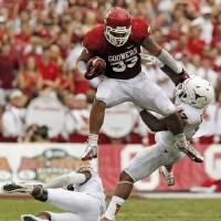Photo - JUMP: OU's Trey Millard (33) leaps over UT's Mykkele Thompson (2) and pushes away Adrian Phillips (17) in the second quarter during the Red River Rivalry college football game between the University of Oklahoma (OU) and the University of Texas (UT) at the Cotton Bowl in Dallas, Saturday, Oct. 13, 2012. OU won, 63-21. Photo by Nate Billings, The Oklahoman