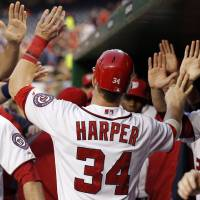 Photo - Washington Nationals' Bryce Harper (34) celebrates with teammates after scoring during the first inning of a baseball game with the Chicago Cubs at Nationals Park, Thursday, Sept. 6, 2012, in Washington. (AP Photo/Alex Brandon)  Alex Brandon