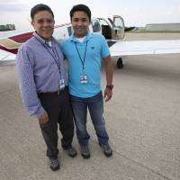 Photo - In this Thursday, June 19, 2014 photo, Babar Suleman and son Haris Suleman, 17, stand next to their plane at an airport in Greenwood, Ind. before taking off for an around-the-world flight. On Wednesday, July 23, 2014, a single-engine plane with two aboard crashed in waters off American Samoa, with a registration number matching the plane flown by the Indiana teen attempting to fly around the world in 30 days. (AP Photo/The Indianapolis Star, Robert Scheer)