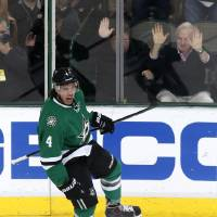 Photo - Dallas Stars defenseman Brenden Dillon (4) celebrates his short-handed goal against the Carolina Hurricanes during the first period of an NHL hockey game on Thursday, Feb. 27, 2014, in Dallas. (AP Photo/Sharon Ellman)