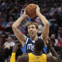 Photo - Dallas Mavericks forward Dirk Nowitzki (41) holds the ball away from Denver Nuggets center J.J. Hickson (7) in the second quarter of an NBA game in Denver on Wednesday, March 5, 2014.(AP Photo/Joe Mahoney)