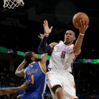 Photo - Oklahoma City's Russell Westbrook (0) leaps past Golden State's Dorell Wright (1) to the basket during the NBA basketball game between the Oklahoma City Thunder and the Golden State Warriors at the Oklahoma City Arena, Tuesday, March 29, 2011. Photo by Bryan Terry, The Oklahoman