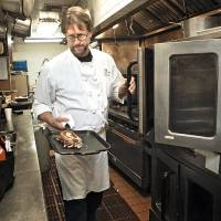 Photo - The Coach House chef Kurt Fleischfresser puts one of the the restaurant's corned beef sandwiches in an oven. PHOTO BY CHRIS LANDSBERGER, THE OKLAHOMAN