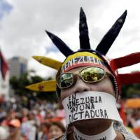 Photo - An opponent of Venezuela's President Hugo Chavez wears a message over his mouth that reads in Spanish,