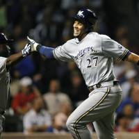Photo - Milwaukee Brewers' Yuniesky Betancourt left, high-fives Carlos Gomez (27) after Gomez scored on a double by Jeff Bianchi against the Chicago Cubs during the ninth inning of a baseball game, Monday, July 29, 2013, in Chicago. (AP Photo/Jim Prisching)