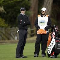 Photo - Jimmy Walker, left, waits to hit from the second fairway Saturday, Feb. 8, 2014, during the third round of the AT&T Pebble Beach Pro-Am golf tournament on the Monterey Peninsula Country Club Shore Course in Pebble Beach, Calif. (AP Photo/Ben Margot)