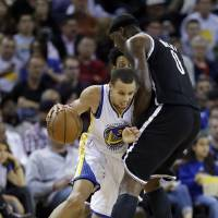 Photo -   Golden State Warriors' Stephen Curry, left, tries to dribble around Brooklyn Nets' Andray Blatche (0) during the first half of an NBA basketball game in Oakland, Calif., Wednesday, Nov. 21, 2012. (AP Photo/Marcio Jose Sanchez)