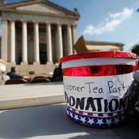 Photo - A donation bucket sits Thursday on a table at a Sooner Tea Party rally outside the Capitol attended by less than 30 people.  JIM BECKEL