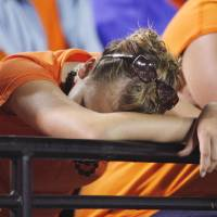 Photo - OSU fan Danielle Brawner hides her head during second half action during the college football game between the Troy University Trojans and the Oklahoma State University Cowboys at Movie Gallery Veterans Stadium in Troy, Ala., Friday, September 14, 2007. BY STEVE SISNEY, THE OKLAHOMAN ORG XMIT: KOD