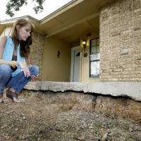 Photo - Barbara Brown poses for a photo by the front step of her home that now sits about one foot off the surface of her lawn, Saturday, June 21, 2014, in Reno, Texas. Brown said that the top of the step once sat about four inches off the surface of her lawn. Brown said she believes the sinkholes on her property and the drop of her lawn have to do with natural gas drilling. (AP Photo/Tony Gutierrez)