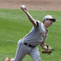 Photo - Texas starting pitcher Parker French works against Louisville in the first inning of an NCAA baseball College World Series elimination game in Omaha, Neb., Monday, June 16, 2014. (AP Photo/Nati Harnik)