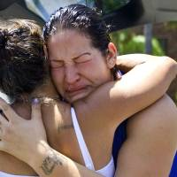 Photo -   Lupe Diaz, right, sister of Manuel Diaz, gets a hug from Theresa Smith during a protest in front of the Anaheim Police Department, Sunday, July 22, 2012, in Anaheim, Calif. Manuel Diaz, an allegedly unarmed man, was shot by Anaheim Police on Saturday, The Orange County Register reports. Smith said her son was also killed by police two years ago. (AP Photo/The Orange County Register, Mindy Schauer) MAGS OUT; LOS ANGELES TIMES OUT.