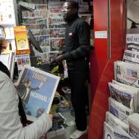 Photo -   A commuter buys a newspaper which fronts a picture of President-elect Francois Hollande in a Paris subway station Monday May 7, 2012. France handed the presidency Sunday to leftist Francois Hollande, a champion of government stimulus programs who says the state should protect the downtrodden, a victory that could deal a death blow to the drive for austerity that has been the hallmark of Europe in recent years. (AP Photo/Peter Dejong)