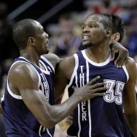 Photo - Oklahoma City Thunder center Serge Ibaka, left, walks teammate Kevin Durant away from the referee after Durant is called for a technical foul during the first half of an NBA basketball game against the Portland Trail Blazers in Portland, Ore., Tuesday, Feb. 11, 2014. (AP Photo/Don Ryan)