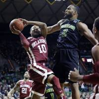 Photo - OU's Jordan Woodard, left, is fouled by Baylor's Rico Gathers during the Sooners' 66-64 win on Saturday in Waco, Texas. AP Photo
