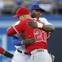 Photo - Los Angeles Angels' Mike Trout, left, and Los Angeles Dodgers' Yasiel Puig embrace before a baseball game, Monday, August 4, 2014, in Los Angeles. (AP Photo/Danny Moloshok)