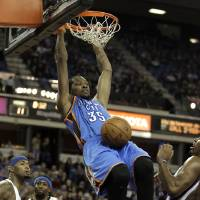 Photo - Oklahoma City Thunder forward Kevin Durant, center, hangs from the rim after stuffing the ball against Sacramento Kings DeMarcus Cousins, left, John Salmons, second from left, and Jason Thompson, right, during the first quarter of  an NBA basketball game in Sacramento, Calif., Friday, Jan. 25, 2013. (AP Photo/Rich Pedroncelli)