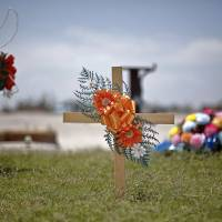 Photo - A cross along with other items have been placed as a memorial to the people killed by the May 20th tornado near the former location of 7-Eleven at the corner of SW 4th St and Telephone Road. Megan Futrell and her four-month-old son Case were two of the victims that were killed when the tornado hit the location.  CHRIS LANDSBERGER - CHRIS LANDSBERGER