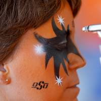 Photo - Joel Atkins of Stillwater gets his face painted before the OSU-Arizona game Thursday night in Stillwater. PHOTO BY BRYAN TERRY, The Oklahoman