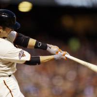 Photo - San Francisco Giants' Buster Posey singles during the fourth inning of a baseball game against the Milwaukee Brewers on Tuesday, Aug. 6, 2013, in San Francisco. (AP Photo/Marcio Jose Sanchez)