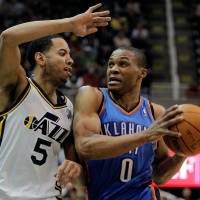 Photo - Oklahoma City Thunder guard Russell Westbrook (0) drives against Utah Jazz guard Devin Harris (5) during the first half of their NBA basketball game in Salt Lake City, Friday, Feb. 10, 2012. (AP Photo/Steve C. Wilson) ORG XMIT: UTSW103