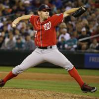 Photo - Washington Nationals starting pitcher Stephen Strasburg throws against the Seattle Mariners in the eighth inning of a baseball game, Saturday, Aug. 30, 2014, in Seattle. Strasburg was the winning pitcher as the Nationals beat the Mariners 3-1. (AP Photo/Ted S. Warren)
