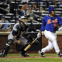 Photo - New York Mets' Bobby Abreu (53) hits an RBI single off of San Diego Padres starting pitcher Andrew Cashner as Rene Rivera catches for the Padres in the fifth inning of a baseball game at Citi Field on Friday, June 13, 2014, in New York. (AP Photo/Kathy Kmonicek)