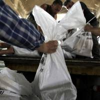Photo -   Workers fill a truck with bags depicting voting papers in Athens' municipality's warehouse, before delivering them to the polling stations around Athens, on Thursday, May 3, 2012. Greeks head to the polls in early general elections on May 6 .(AP Photo/Petros Giannakouris)