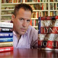 Photo - FILE - In a Sept. 2, 2005 file photo, best-selling author Vince Flynn poses with the dust jacket of his new book,