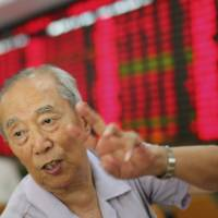 Photo - An investor gestures at a private securities company on Monday July 15, 2013 in Shanghai, China. Asian stock markets posted modest gains Monday, registering relief that a slowdown in China's economic growth wasn't as sharp as feared. (AP Photo)