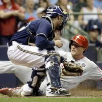 Photo - Philadelphia Phillies' Cody Asche slides safely past Milwaukee Brewers catcher Jonathan Lucroy during the fifth inning of a baseball game Tuesday, July 8, 2014, in Milwaukee. Asche scored from second on a hit by Domonic Brown. (AP Photo/Morry Gash)
