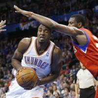 Photo - Oklahoma City Thunder forward Serge Ibaka (9) is fouled by Philadelphia 76ers forward Thaddeus Young (21) as he drives the to basket in the third quarter of an NBA basketball game in Oklahoma City, Friday, Jan. 4, 2013. Oklahoma City won 109-85. (AP Photo/Sue Ogrocki)