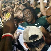 Photo - Baylor's Robert Griffin III (10) is surrounded by fans as he tries to leave the field after the college football game in which the University of Oklahoma Sooners (OU) were defeated 45-38 by the Baylor Bears (BU) at Floyd Casey Stadium on Saturday, Nov. 19, 2011, in Waco, Texas.   Photo by Steve Sisney, The Oklahoman ORG XMIT: KOD
