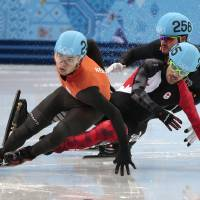 Photo - Charles Hamelin of Canada, centre, crashes out with Eduardo Alvarez of the United States, right, as they compete with Sjinkie Knegt of Netherlands in a men's 1000m short track speedskating quarterfinal at the Iceberg Skating Palace during the 2014 Winter Olympics, Saturday, Feb. 15, 2014, in Sochi, Russia. (AP Photo/Ivan Sekretarev)