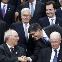 Photo - U.S. Treasury Secretary Jack Lew, right, shakes hands with German's Finance Minister Wolfgang Schaeuble during a group photo of the G20 finance ministers and central bank governors on the sidelines of their meeting at World Bank Group International Monetary Fund Spring Meetings in Washington, Friday, April 19, 2013. Also pictured are Britain's Chancellor of the Exchequer George Osborne, top right, and Bank of England Gov. Mervyn King, top row center. (AP Photo/Charles Dharapak)