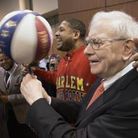 "Photo - Berkshire Hathaway Chairman and CEO Warren Buffett, right, is watched by Detroit Lions defensive tackle Ndamukong Suh, left, as he is assisted by Harlem Globetrotter Chris ""Handles"" Franklin in spinning a basketball in Omaha, Neb., Saturday, May 4, 2013, before holding the Berkshire Hathaway shareholders meeting. Tens of thousands attend Berkshire Hathaway shareholder meeting to hear Warren Buffett and Charlie Munger answer questions for more than six hours. No other annual meeting can rival Berkshire's, which is known for its size, the straight talk Buffett and Munger offer and the sales records shareholders set while buying Berkshire products. (AP Photo/Nati Harnik)"