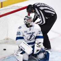 Photo - The linesman retrieves the puck in the net behind Tampa Bay Lightning goalie Ben Bishop following a power-play goal by Montreal Canadiens' Brian Gionta during the third period of their NHL hockey game, Thursday, April 18, 2013, in Montreal. The Canadiens won 3-2. (AP Photo/The Canadian Press, Paul Chiasson)