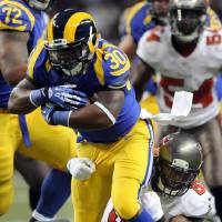 Photo - St. Louis Rams running back Zac Stacy (30) runs with the ball as Tampa Bay Buccaneers linebacker Mason Foster defends during the first quarter of an NFL football game on Sunday, Dec. 22, 2013, in St. Louis. (AP Photo/L.G. Patterson)