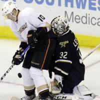 Photo - Dallas Stars goalie Kari Lehtonen (32) defends the goal against Anaheim Ducks right wing Corey Perry (10) during the first period of an NHL hockey game on Friday, Feb. 8, 2013, in Dallas. (AP Photo/LM Otero)
