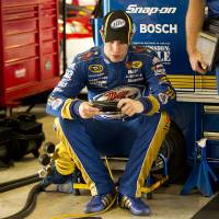 Photo -   Brad Keselowski sends messages on his phone as his crew works on his car during the practice session for Sunday's NASCAR Sprint Cup Series auto race, Sunday, at the Homestead-Miami Speedway in Homestead, Fla., Friday, Nov. 16, 2012. (AP Photo/JPat Carter)