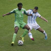 Photo - Nigeria's Efe Ambrose, left, and Argentina's Sergio Aguero battle for the ball during the group F World Cup soccer match between Nigeria and Argentina at the Estadio Beira-Rio in Porto Alegre, Brazil, Wednesday, June 25, 2014. (AP Photo/Michael Sohn)