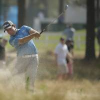 Photo - Erik Compton hits from the natural area on the 12th hole during the third round of the U.S. Open golf tournament in Pinehurst, N.C., Saturday, June 14, 2014. (AP Photo/Charlie Riedel)