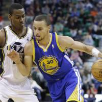 Photo - Utah Jazz's Alec Burks, left, defends against Golden State Warriors' Stephen Curry (30) as he drives in the second quarter during an NBA basketball game Monday, Nov. 18, 2013, in Salt Lake City. (AP Photo/Rick Bowmer)